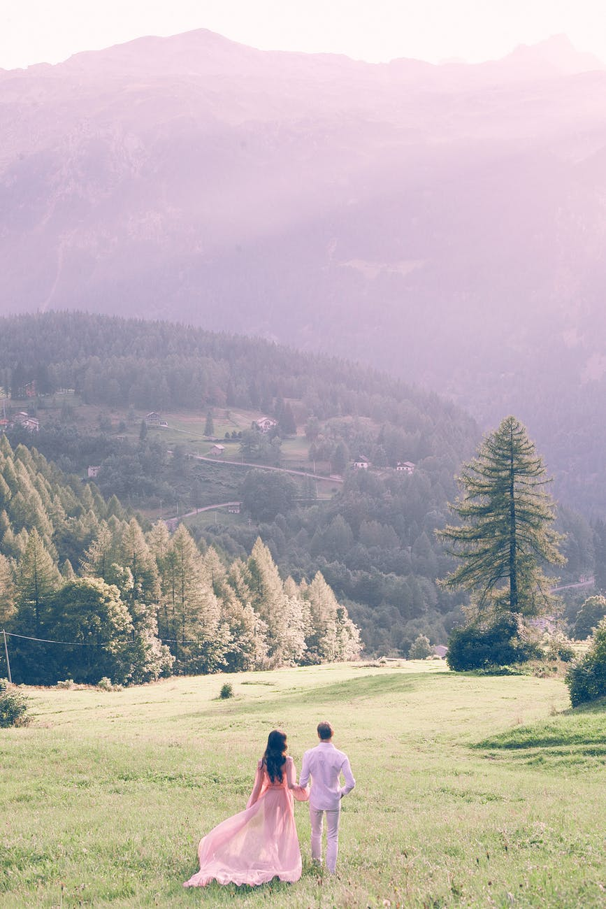 unrecognizable newlywed couple strolling in field against mountains